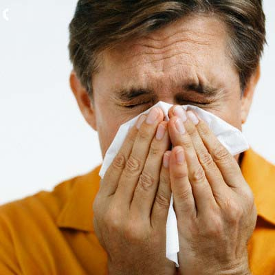 Man Sneezing --- Image by © Sean Justice/Corbis