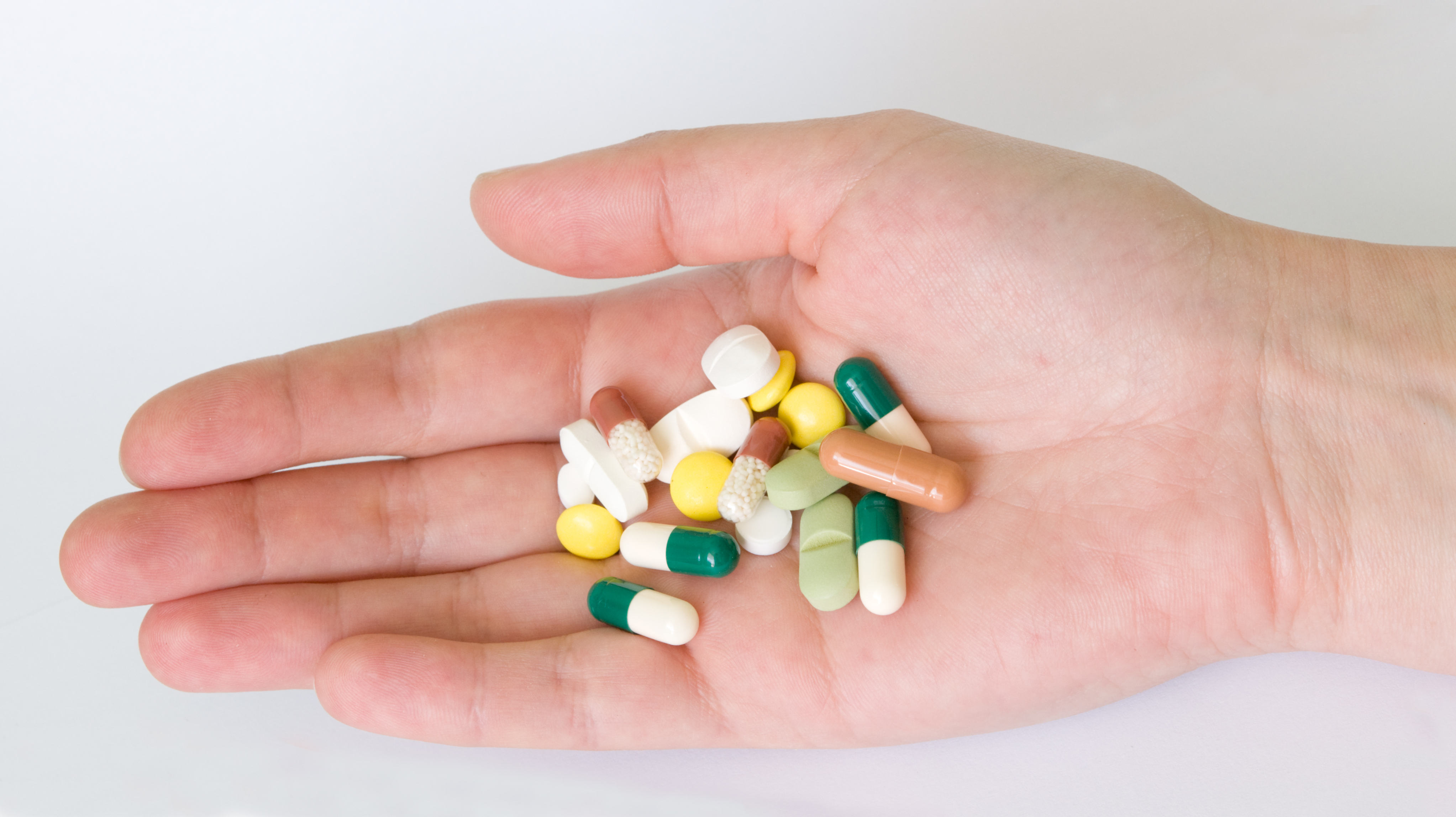 Hand with different forms and colours pills and capsules